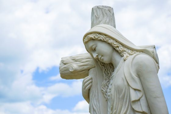 Religious sculpture of a woman carrying a cross.